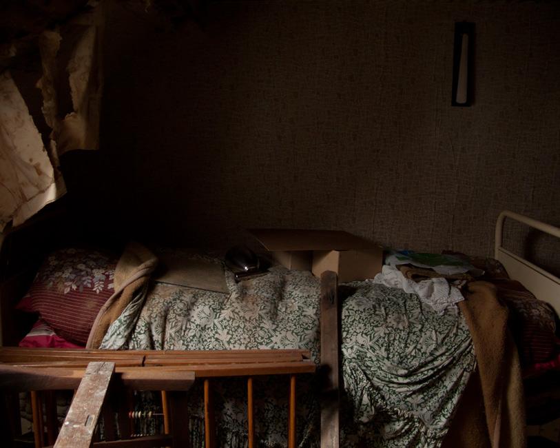 Stille Kammern - Haubarg, Dachkammer, 2012, Fotografie, 50 x 70 cm, Zu sehen das Interieur der Dachkammer des verlassenen Haubargs auf Eiderstedt. Bett, Kinderbett, Kleiderbürste, Kartons, Stoffe. Malerisch muten die Faltenwürfe und Tapentfetzen, die von der Wand hängen, an. Die Wohn- und Lagerräume des friesischen Bauernhauses vermitteln den Eindruck, als währen die Bewohner noch anwesend. Ihre Spuren stammen aus unterschiedlichen Zeiten. Anna Ullrich, Das Copyright © 2012 des Bildes liegt bei Anna Ullrich. Alle Rechte vorbehalten.