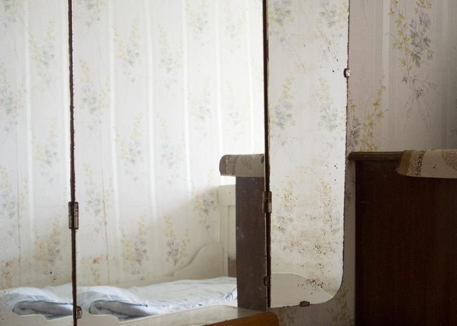 Stille Kammern - Haubarg, Kinderzimmer, 2014, Fotografie, 50 x 70 cm, Zu sehen ist der der Blick in einen dreigeteilten Spiegel im Kinderzimmer. Die Wohn- und Lagerräume des friesischen Bauernhauses vermitteln den Eindruck, als währen die Bewohner noch anwesend. Ihre Spuren stammen aus unterschiedlichen Zeiten. Anna Ullrich, Das Copyright © 2014 des Bildes liegt bei Anna Ullrich. Alle Rechte vorbehalten.