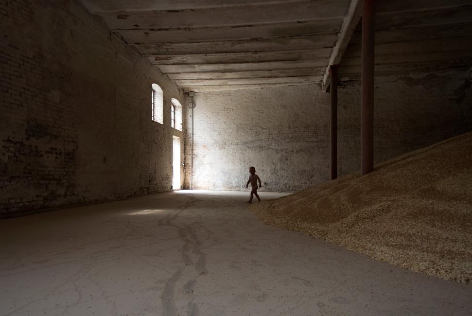 Täglich Brot, Serie 2, Ernte 2016, Bild 1, Fotografie, 40 x 60 cm, Zu sehen ist ein kleiner, nackter Mensch vor dem raumfüllenden Getreideberg. Jakob, der Sohn des Landwirtes. Die Motive der Serie entstanden bei Begleitung der Getreideernte 2016. Der Serie zu Grunde liegt die Frage danach, was für den Menschen in Wirklichkeit wichtig ist, wovon er lebt, was er braucht und wie er seine Wahrnehmung beschaffen ist. Anna Ullrich, Das Copyright © 2016 des Bildes liegt bei Anna Ullrich. Alle Rechte vorbehalten.