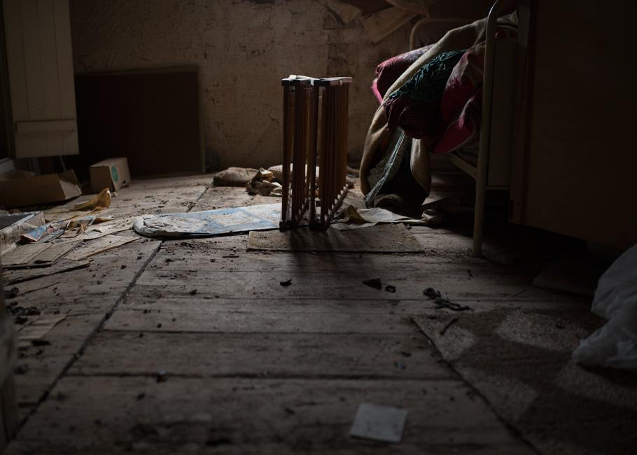 Stille Kammern - Haubarg, Dachboden, 2018, Fotografie, 50 x 70 cm, Zu sehen ist der Zustand der Verlassenheit auf dem Dachboden des verlassenen Haubargs auf Eiderstedt. In der Mitte des Raumes stand 2012 ein Stuhl, vor ihm langen alte Zeitungen. Beides ist verschwunden. Das Kinderbett steht nun im Zentrum. Die Wohn- und Lagerräume des friesischen Bauernhauses vermitteln den Eindruck, als währen die Bewohner noch anwesend. Ihre Spuren stammen aus unterschiedlichen Zeiten. Anna Ullrich, Das Copyright © 2012 des Bildes liegt bei Anna Ullrich. Alle Rechte vorbehalten.
