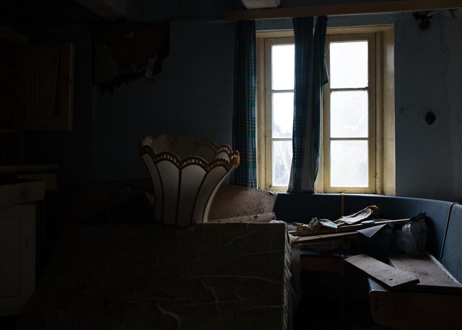 Stille Kammern - Haubarg, Küche, 2018, Fotografie, 50 x 70 cm, Zu sehen ist die Sitzecke in der blau gestrichenen Küche. Auf dem Tisch liegt kopfüber ein Lampenschirm aus dem Wohnzimmer. Die Wohn- und Lagerräume des friesischen Bauernhauses vermitteln den Eindruck, als währen die Bewohner noch anwesend. Ihre Spuren stammen aus unterschiedlichen Zeiten. Anna Ullrich, Das Copyright © 2018 des Bildes liegt bei Anna Ullrich. Alle Rechte vorbehalten.