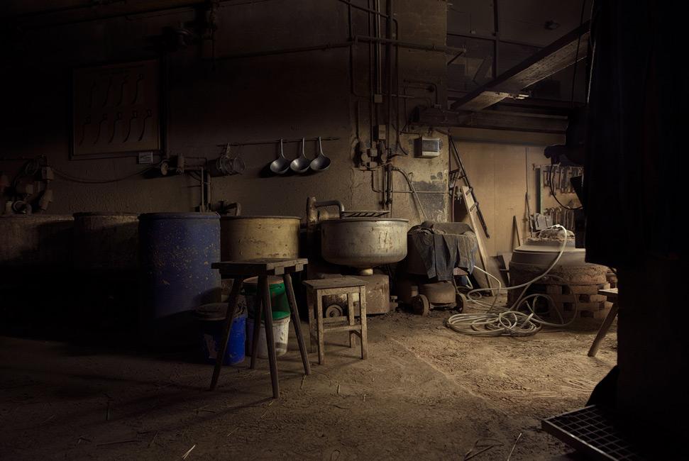 Täglich Brot, Artfremd, Serie 4, 2019, Fotografie, 70 x 100 cm, Zu sehen sind Teigrührmaschinen in einer Glockengießerei. Dieses Motiv erweitert das Thema der Serie um das Motiv Arbeit als tägliches Brot. Die Bottiche, in denen früher Teig gemischt wurde schlagen wiederum die Brücke zum Thema des Getreides sowie der Ernte. Die Motive der Serie entstanden 2019. Der Serie zu Grunde liegt die Frage danach, was für den Menschen in Wirklichkeit wichtig ist, wovon er lebt, was er braucht und wie er seine Wahrnehmung beschaffen ist. Anna Ullrich, Das Copyright © 2019 des Bildes liegt bei Anna Ullrich. Alle Rechte vorbehalten.